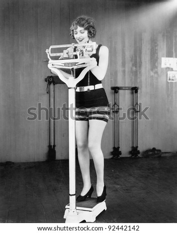 Young woman on a scale taking her weight - stock photo