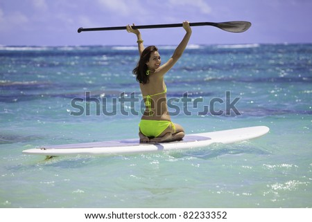 young woman on a stand up paddle board - stock photo