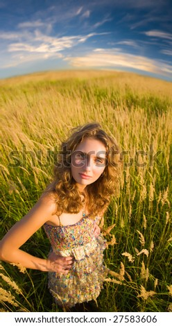 Young woman on a summer field. Wide angle view.