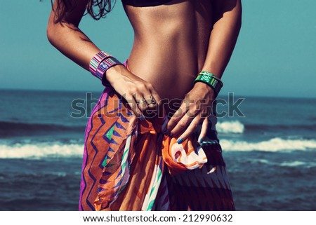 young woman on beach tiedown colorful sarong wearing beautiful braceletes closeup - stock photo