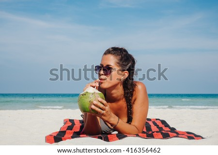 Young woman on beach with coconut - stock photo