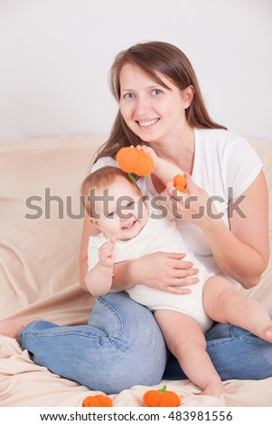 Young woman on bed, having fun playing with a child crochet pumpkin amigurumi