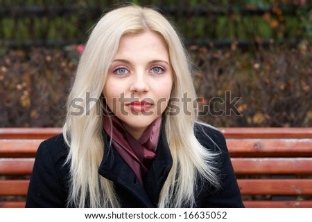 Young woman on bench, looking at camera - stock photo