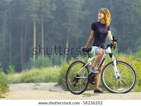 Young woman on bike standing on road and looking to somewhere - stock photo