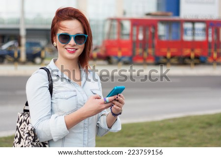 Young woman on city street using smart phone - stock photo