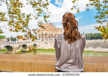 Young woman on embankment looking on castel sant'angelo in rome italy. rear view - stock photo