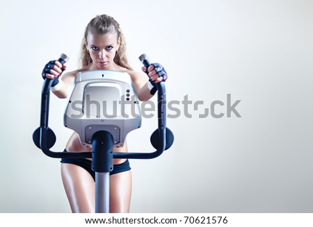 Young woman on exercise bicycle on wall background. - stock photo