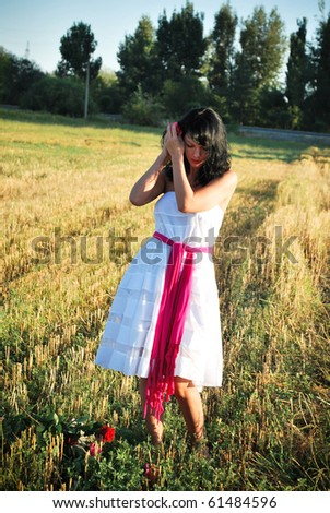 young woman on field with  rose in hair - stock photo