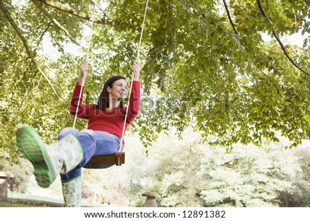Young woman on garden swing - stock photo