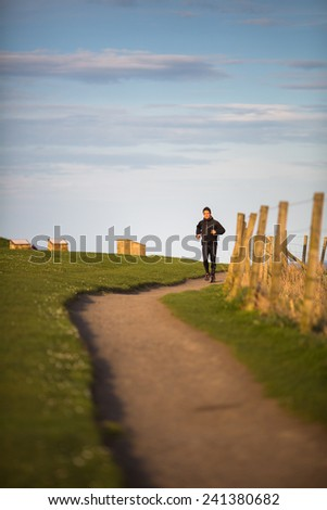 Young woman on her evening jog along the seacoast - stock photo