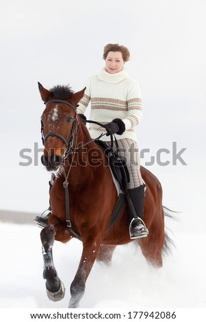 Young woman on horseback at winter day