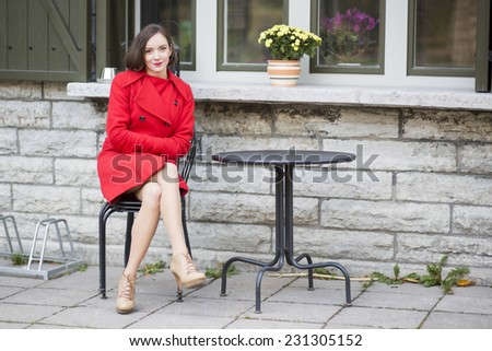 Young woman on metal chair at street cafe  - stock photo
