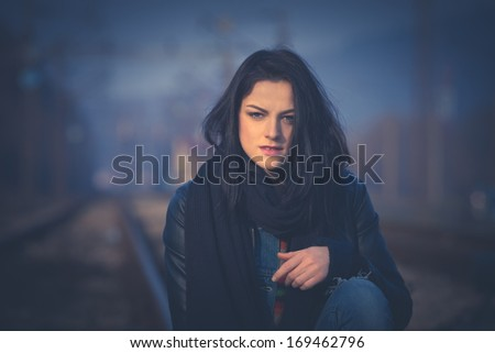 young woman on railroad, portrait,   retro colors - stock photo