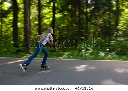 Young woman on rollerbaldes skating at summer park