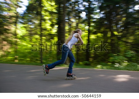 Young woman on rollerbaldes skating at summer park - stock photo