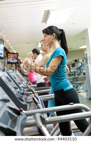 young woman on running treadmill at gym - stock photo