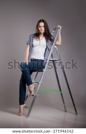 Young woman on step ladder. Isolated on white. - stock photo