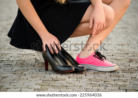 Young woman  on street in sneakers and high heels shoes are next to her - stock photo