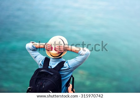 young woman on summer vacation, hiking on coastline and staring at sea wearing hat and backpack. Travel and adventure concept  - stock photo