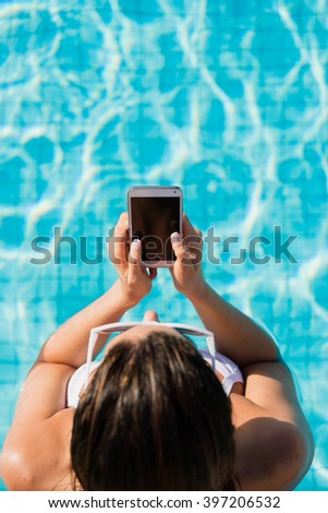 Young woman on summer vacation texting or messaging on smartphone in swimming pool. - stock photo