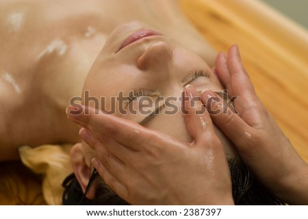 young woman on the ayurvedic aromatherapy oil massage procedure - stock photo