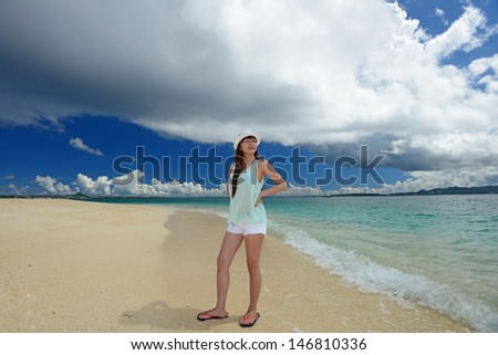 Young woman on the beach enjoy sunlight - stock photo