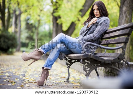 Young woman on the bench in the park - stock photo