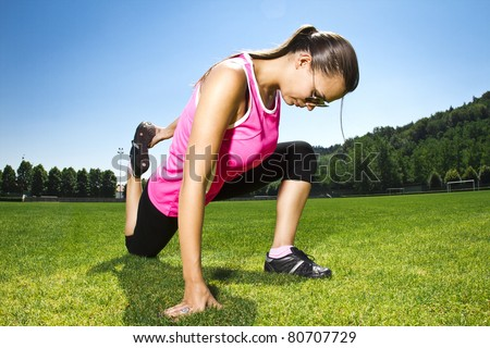 Young woman on the freshly cut grass stretching after exercise