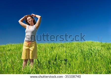 Young woman on the green field stretching hands - stock photo