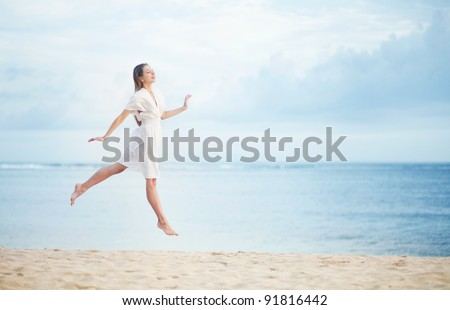 Young woman on the ocean shore in white dress - stock photo