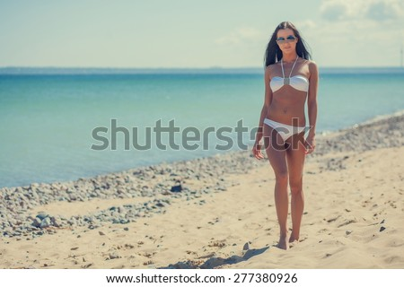 young woman on the sea in a white bikini