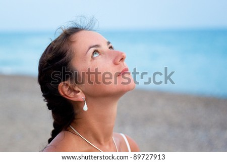 Young woman  on the sea shore looking on the sky - stock photo