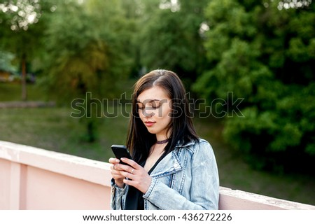 Young woman on the street walking and texting on the smart phone