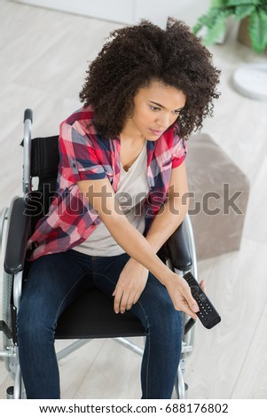 young woman on the wheelchair watching television