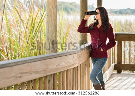 Young woman on wooden nature trail with binoculars in early autumn - stock photo