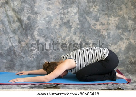Young woman on yoga mat  doing Yoga posture Balasana or child's pose against a grey background in profile, facing left lit by diffused sunlight. - stock photo