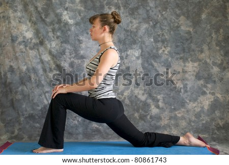 Young woman on yoga mat in woman doing Yoga posture Low Lunge or Ashwa Sanchalanasana with hands on knee, against a grey background in profile, facing left lit by diffused sunlight. - stock photo