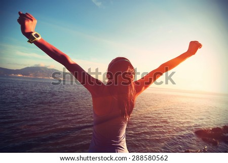 young woman open arms at sunrise seaside - stock photo