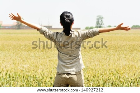 young woman open arms at wheat field - stock photo