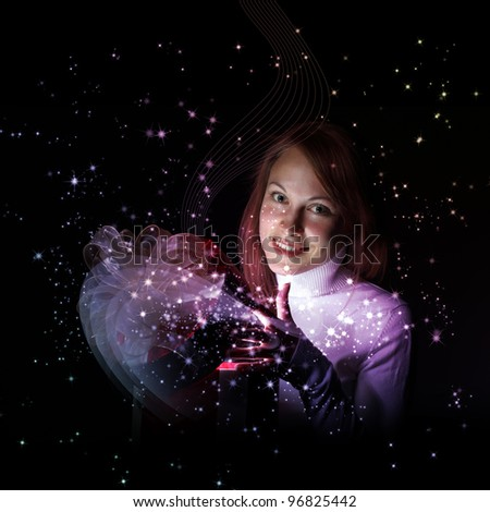 Young woman opening a gift box with shining and glittering lights around her - stock photo