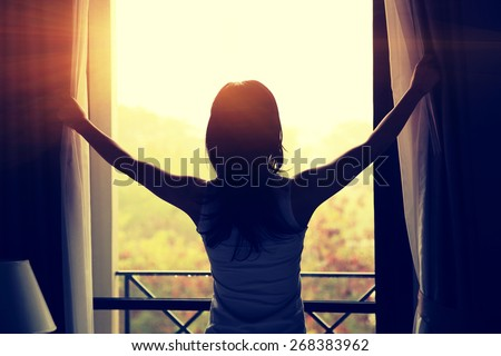 young woman opening curtains in a bedroom - stock photo
