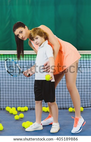 Young woman or coach teaching child how to play tennis on a court indoor - stock photo