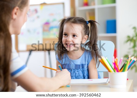 Young woman or mother teaches kid to pencil - stock photo