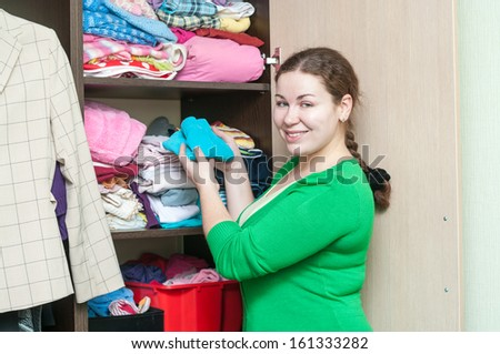 Young woman organizing clothes in the wardrobe closet at home - stock photo