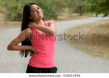 Young woman out jogging suffers a muscle injury standing holding her neck and lower back while grimacing in pain on a rural road, close up upper body view - stock photo