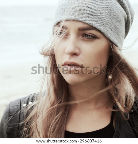 Young woman outdoor summer sensual sad mood cold weather portrait posing on the wind in hat  - stock photo