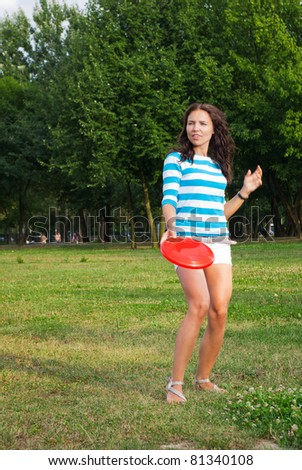 Young woman outdoor tossing a frisbee - stock photo