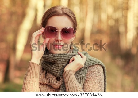 Young woman outdoors autumn fashion portrait with scarf and sunglasses - stock photo