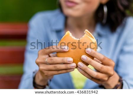 young woman outdoors eating a fast food hamburger - stock photo