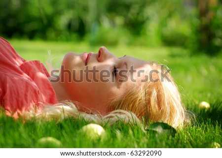 Young woman outdoors lying on the grass - stock photo